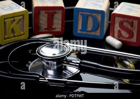 Kids health care concept with block letters and stethoscope. Block letters spelling the word KIDS with doctor tools in the foreground. Health care for - Stock Photo