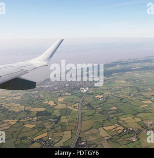 Aerial View of Bristol City Center in England, UK  and surrounding fields. On the left the airplane wing. - Stock Photo