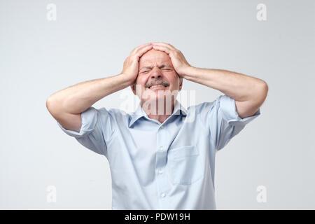 Caucasian senior man having terrible headache. Problem with health at old age - Stock Photo