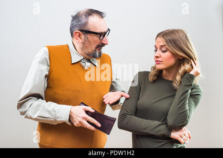 Nerdy man is showing to his beautiful wife that he doesn't have any more money and she is disappointed. - Stock Photo