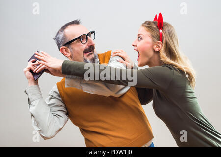 Nerdy man is trying to hide money from his wife because she want to spend it all. - Stock Photo