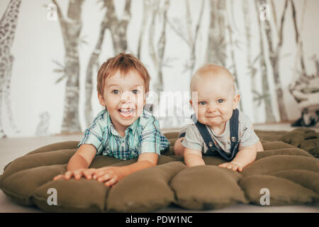 Two brothers lie on carpet, have fun and play. - Stock Photo