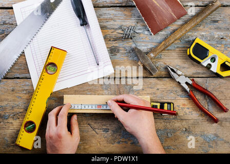 Male hands working on carpenter's desk and working tools. - Stock Photo