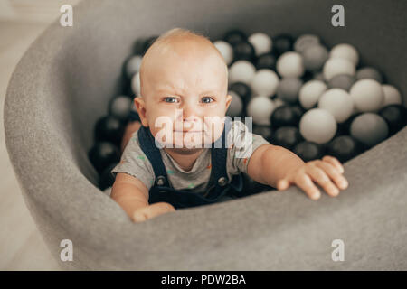 Tearful toddler stands in basket with small balls and cries. Top view. - Stock Photo