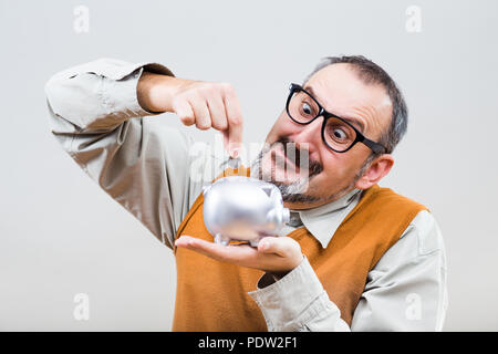 Nerdy man is putting coin into piggy bank. - Stock Photo