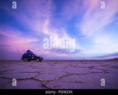 4WD jeep on the horizon of Salar de Uyuni Salt Flat in Bolivia - Stock Photo