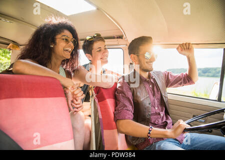 Mixed group of young people going on holiday in a camper van - Stock Photo