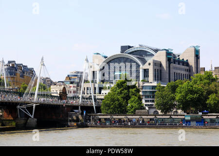 Charing Cross railway station on the north bank of the River Thames, London. Hungerford and Golden Jubilee bridge with crowds of tourists. - Stock Photo