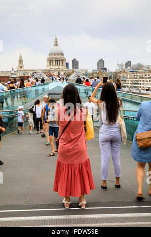 Female tourists stop to take photographs on London's Millenium Bridge looking towards St Pauls Cathedral. London, England - Stock Photo