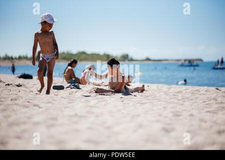Kids playing on a Issyk Kul lake beach in Kyrgyzstan. - Stock Photo