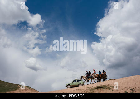 Riding horses in Kyrgyzstan - Stock Photo