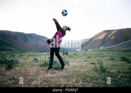 A girl playing volleyball on a field in Kyrgyzstan - Stock Photo