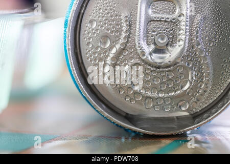 Detail of a can of beverage on a restaurant table. Condensate water bubble on drink, close up. - Stock Photo