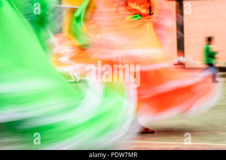 Swirling skirts of traditional folk dancers from El Salvador caught in blur of color and movement. - Stock Photo