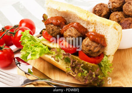 Homemade spicy meatball sub sandwich with marinara sauce and tomatoes - Stock Photo