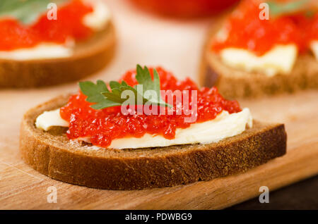 Sandwiches with imitation red caviar and butter on wooden cutting board on wooden table - Stock Photo