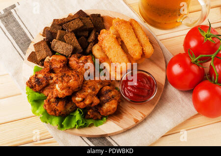 Fried wings, dried bread and cheese sticks with mug beer, served with sauces on a wooden background - Stock Photo