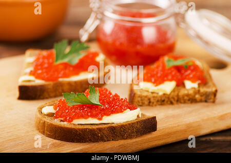 Red salmon caviar in sandwich and glass jar on a wooden table - Stock Photo