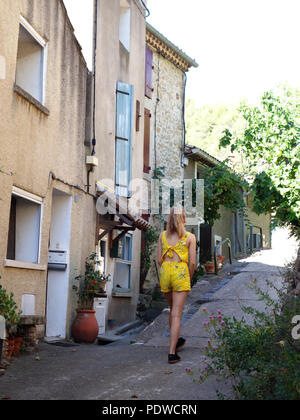 A cheerful and brightly dressed 16 year old blond haired girl walking through the old village streets of Cessenon walking away from the camera - Stock Photo
