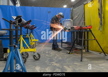 Man working with metal pipes grinding - Stock Photo
