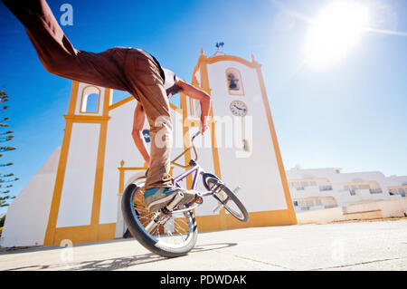 young man have fun doing tricks with freestlye bike in a sware in front of a church. contrast between classic and modern related lifestyle. sunny day  - Stock Photo