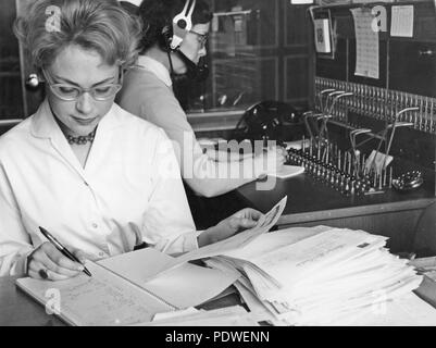 1950s office clerk and telephone switchboard operator. A young office worker is sitting at her desk handling documents. A telephone operator is sitting behind her taking incoming calls and connecting them further. 1958 - Stock Photo