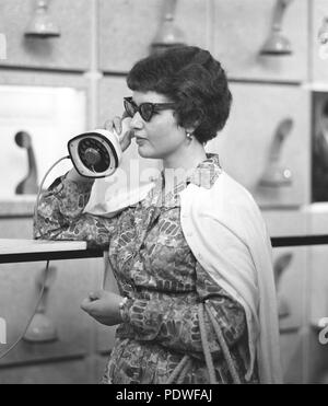 1950s glasses and telephone. A young woman in typical fifties glasses and bows is talking on the telephone.  Swedish on-piece plastic telephone created by Ericsson Company of Sweden and launched 1956. Because of its styling and its influence on future telephone design, the Ericofon is considered one of the most significant industrial designs of the 20th century. The idea was to incorporate the dial and handset into one single unit. To call, you lifted it up and dialed the number, and to end the call, you put the phone down.  known as the Cobra telephone for its snakelike shape - Stock Photo