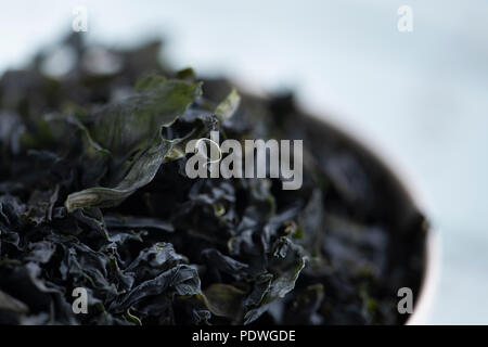 closeup of a pile of dried leaves of wakame, an Asian edible seaweed used in traditional soups such as the miso soup, on a white ceramic bowl - Stock Photo