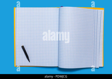Black used pencil lying on a copybook - Stock Photo