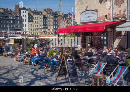 Sitting out in the winter sun at a cafe by the old harbour, Vieux Bassin, in Honfleur, Normandy, France - Stock Photo