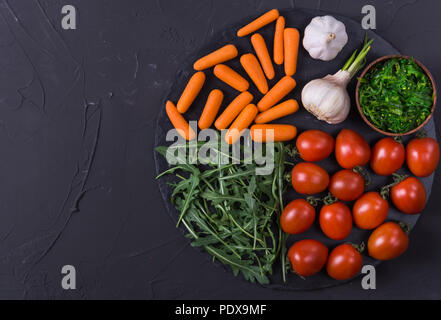 Fresh ingredients for cooking in rustic setting: tomatoes,arugula, carrot, garlic and seaweed - Stock Photo
