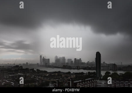 London, UK. 10th August, 2018. UK Weather: Heavy rainstorm and fast moving clouds over the city including Canary Wharf business park buildings. Credit: Guy Corbishley/Alamy Live News - Stock Photo
