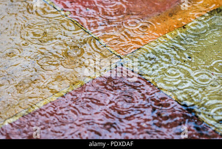 Woking, Surrey, England, UK, 10th August 2018. Heavy rain showers  fall in Woking, Surrey, south-east England after a period of prolonged drought. The shower and falling raindrops splash and make ripples in standing water on the colourful paving slabs of a garden patio. Credit: Graham Prentice/Alamy Live News. - Stock Photo