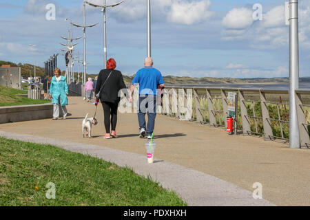 Newcastle, County Down, Northern Ireland. 10 August 2018. UK weather - an improving picture across County Down this afternoon with heavy showers giving way to sunny periods. Tomorrow (Saturday) sees the annual Newcastle Festival of Flight take place at the seaside town. People out walking on the promenade enjoying the late afternnon sunshine. Copyright David Hunter/Alamy Live News. - Stock Photo
