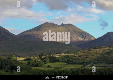 Newcastle, County Down, Northern Ireland. 10 August 2018. UK weather - an improving picture across County Down this afternoon with heavy showers giving way to sunny periods. Tomorrow (Saturday) sees the annual Newcastle Festival of Flight take place at the seaside town. Late evening sunshine on Slieve Bearnagh in the Mountains of Mourne. Copyright David Hunter/Alamy Live News. - Stock Photo