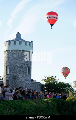 Bristol, United Kingdom, 11 August 2018.  Spectators and photographers line up by The Observatory to watch a mass ascent of hot air balloons during the Bristol International Balloon Fiesta.  The Fiesta, celebrating its 40th anniversary, runs from 9-12 August.  Credit: mfimage/Alamy Live News - Stock Photo