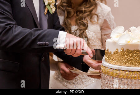 Close-up of a newlywed couple's hands cutting their wedding cake. - Stock Photo