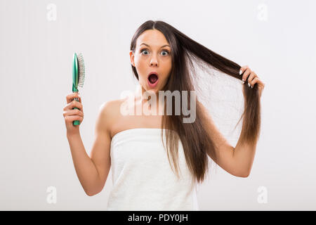 Beautiful woman in panic because of hair loss looking at camera. - Stock Photo