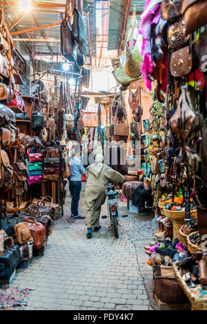 Local with a motorcycle, Narrow streets with leather goods in an Arabian market, Shouk, Fez Medina, Fes, Morocco - Stock Photo