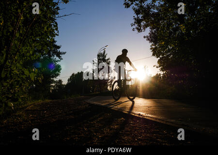 Image of bicyclist wearing helmet riding around city in evening - Stock Photo