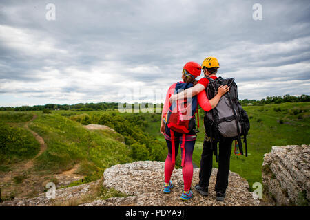 Photo from back of young man and woman with backpacks on top of hill against backdrop of picturesque countryside and gloomy sky - Stock Photo