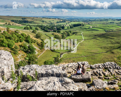 Couple sitting admiring the view over malhamdale from Malham Cove near Malham Yorkshire Dales England - Stock Photo