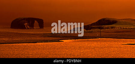 Dore Holm, small islet with natural arch off the coast of Stenness, Esha Ness / Eshaness at sunset on Mainland Shetland, Scotland, UK - Stock Photo