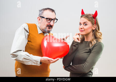 Nerdy man is uncertain in his girlfriend love. - Stock Photo