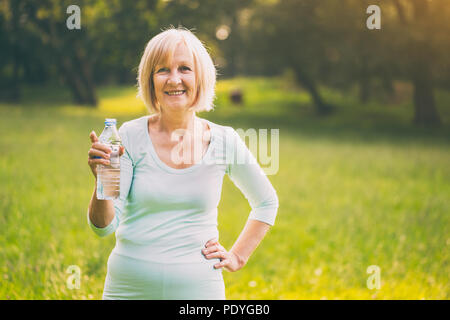 Active senior woman drinking water during exercise.Image is intentionally toned. - Stock Photo