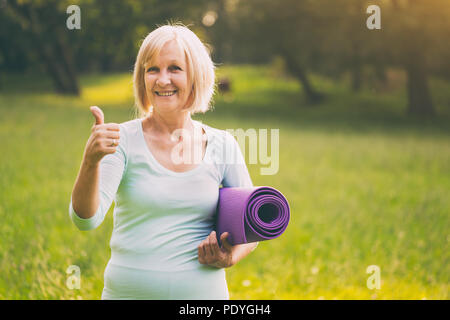 Portrait of sporty senior woman showing thumb up and holding mat in the nature.Image is intentionally toned. - Stock Photo