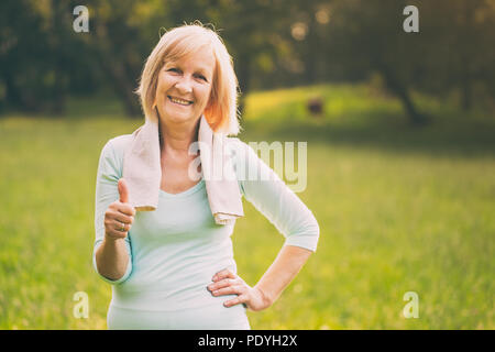 Portrait of sporty senior woman showing thumb up and standing in the nature.Image is intentionally toned. - Stock Photo