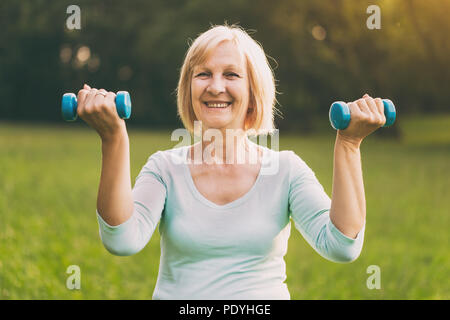 Sporty senior woman exercising with weights outdoor.Image is intentionally toned.