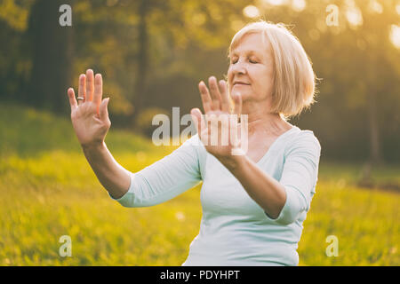 Senior woman enjoys exercise Tai Chi in the nature.Image is intentionally toned. - Stock Photo