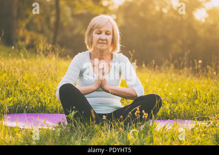 Senior woman enjoys meditating in the nature.Image is intentionally toned. - Stock Photo